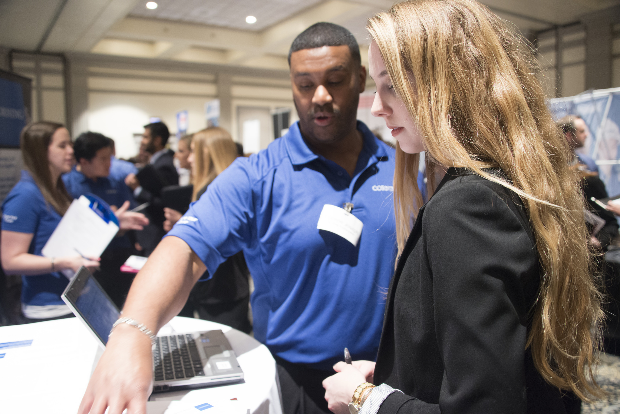 Student attends a career fair and discusses her resume with a recruiter.
